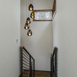 Foto de escalera suspendida, contemporánea, de tamaño medio, con escalones de madera, contrahuellas de madera y barandilla de metal