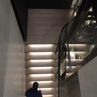 デンバーの巨大な木のモダンスタイルのおしゃれな階段 (ガラスの手すり) の写真