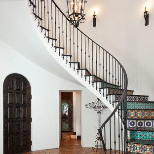 Imagen de escalera curva, mediterránea, con contrahuellas con baldosas y/o azulejos y barandilla de metal