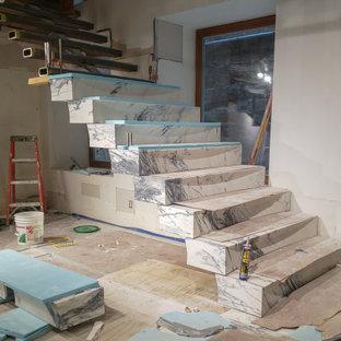 Ispirazione per un'ampia scala sospesa minimalista con pedata in marmo e alzata in marmo