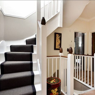 Inspiration for a mid-sized timeless painted spiral wood railing staircase remodel in London with painted risers