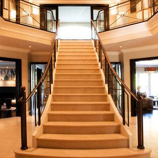 Ejemplo de escalera curva, clásica renovada, con escalones de piedra caliza, contrahuellas de piedra caliza y barandilla de vidrio