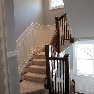 Diseño de escalera en L, tradicional, de tamaño medio, con escalones enmoquetados, contrahuellas de madera pintada y barandilla de madera