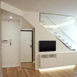 Diseño de escalera en L, actual, de tamaño medio, con escalones de travertino, contrahuellas de travertino y barandilla de vidrio