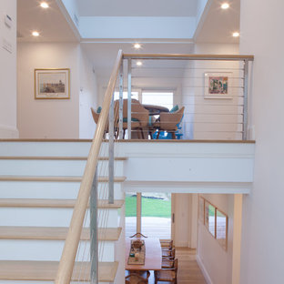 Example of a mid-sized beach style wooden u-shaped cable railing staircase design in Boston with painted risers