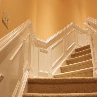 Imagen de escalera suspendida, clásica, de tamaño medio, con escalones enmoquetados, contrahuellas enmoquetadas y barandilla de madera