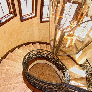 Ejemplo de escalera suspendida, mediterránea, grande, con escalones de travertino, contrahuellas con baldosas y/o azulejos y barandilla de metal