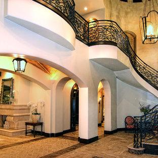 Foto de escalera suspendida, mediterránea, extra grande, con escalones de travertino, contrahuellas con baldosas y/o azulejos y barandilla de metal