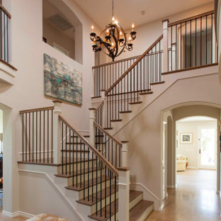 Elegant wooden u-shaped mixed material railing staircase photo in San Diego with painted risers