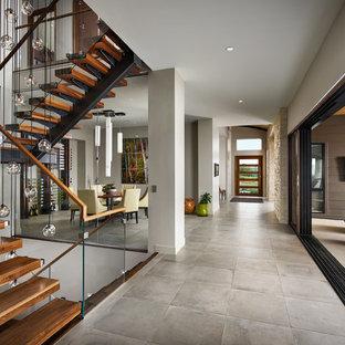 Idee per un'ampia scala sospesa moderna con pedata in legno, nessuna alzata e parapetto in vetro