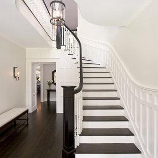 Modelo de escalera curva, tradicional, grande, con escalones de madera, barandilla de madera y contrahuellas de madera pintada