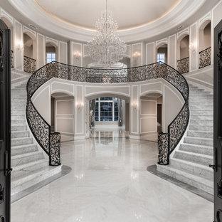 Idee per un'ampia scala curva minimalista con pedata in marmo, alzata in marmo e parapetto in metallo