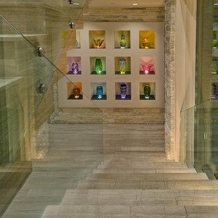 На фото: лестница на больцах в современном стиле с ступенями из известняка, подступенками из известняка и стеклянными перилами с