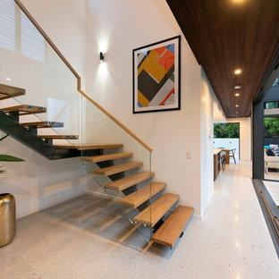 Создайте стильный интерьер: изогнутая лестница среднего размера в современном стиле с деревянными ступенями, стеклянными подступенками и деревянными перилами - последний тренд