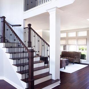 На фото: изогнутая лестница среднего размера в стиле современная классика с деревянными ступенями, крашенными деревянными подступенками и перилами из смешанных материалов с
