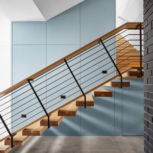 オースティンの広い木のミッドセンチュリースタイルのおしゃれな階段 (混合材の手すり、パネル壁) の写真