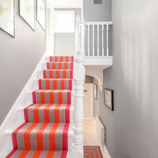 Modelo de escalera en U, nórdica, con escalones de madera pintada, contrahuellas de madera pintada y barandilla de madera