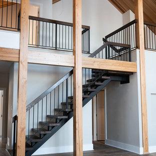 Modelo de escalera suspendida, actual, con escalones de madera, contrahuellas de metal y barandilla de varios materiales