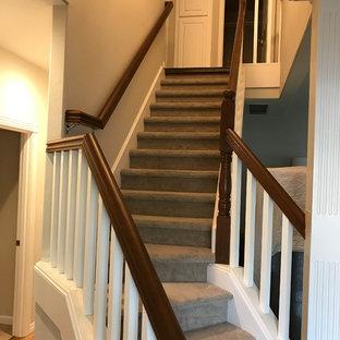 Ejemplo de escalera en L, de estilo americano, de tamaño medio, con escalones enmoquetados, contrahuellas de hormigón y barandilla de madera