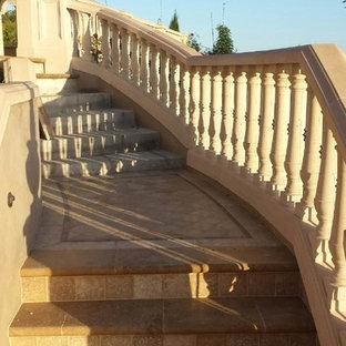 ロサンゼルスの中サイズのタイルの地中海スタイルのおしゃれなサーキュラー階段 (混合材の手すり、タイルの蹴込み板) の写真