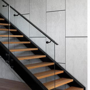 メルボルンの中くらいの木のコンテンポラリースタイルのおしゃれな直階段 (金属の手すり、パネル壁) の写真