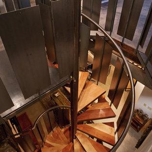 Esempio di una scala a chiocciola industriale di medie dimensioni con pedata in legno e nessuna alzata