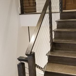 Modelo de escalera en U, de estilo de casa de campo, grande, con escalones de madera, contrahuellas de madera y barandilla de cable