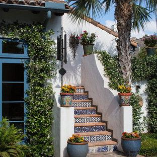 Неиссякаемый источник вдохновения для домашнего уюта: большая изогнутая лестница в средиземноморском стиле с подступенками из плитки и ступенями из терракотовой плитки