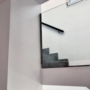 Exempel på en stor modern rak trappa, med klinker, sättsteg i kakel och räcke i glas