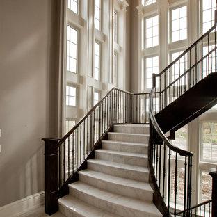 Esempio di un'ampia scala curva tradizionale con parapetto in metallo, pedata in marmo e alzata in marmo