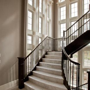 トロントの巨大な大理石のトラディショナルスタイルのおしゃれなかね折れ階段 (大理石の蹴込み板) の写真