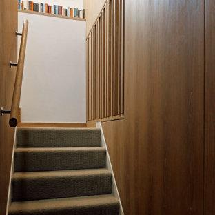 Ejemplo de escalera en U y madera, contemporánea, de tamaño medio, con escalones enmoquetados, barandilla de madera y madera