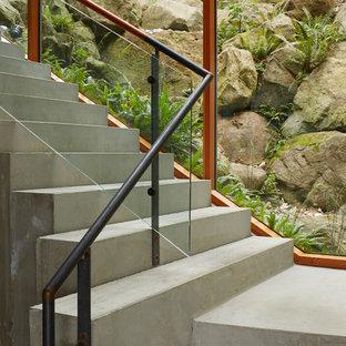 Diseño de escalera en L, contemporánea, con escalones de hormigón, contrahuellas de hormigón y barandilla de vidrio
