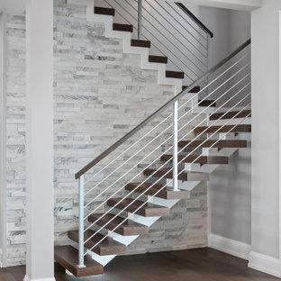 Exemple d'un grand escalier sans contremarche tendance en U avec des marches en bois, un garde-corps en matériaux mixtes et un mur en parement de brique.