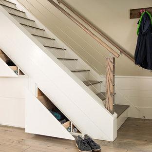 На фото: прямая лестница среднего размера в морском стиле с перилами из тросов, деревянными ступенями и крашенными деревянными подступенками с