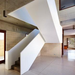 シドニーのコンクリートのコンテンポラリースタイルのおしゃれな折り返し階段 (コンクリートの蹴込み板、木材の手すり) の写真