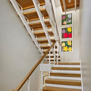 """Foto di una scala a """"U"""" contemporanea di medie dimensioni con pedata in legno, nessuna alzata e parapetto in metallo"""