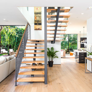 Example of a coastal wooden u-shaped open and cable railing staircase design in Tampa