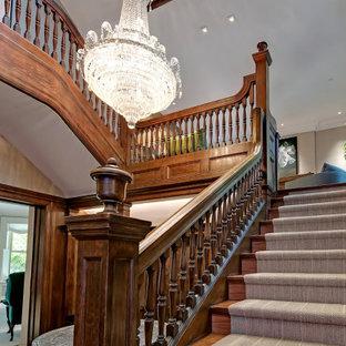 Exemple d'un très grand escalier victorien en U avec des marches en bois, des contremarches en bois et un garde-corps en bois.
