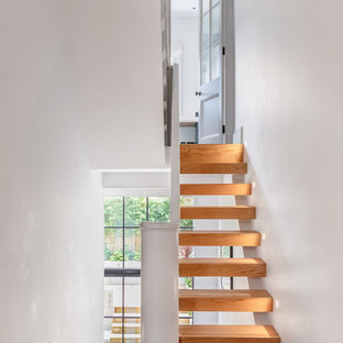 This is an example of a contemporary wood floating staircase in London with open risers.
