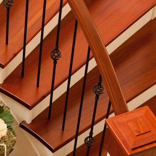 バンクーバーの大きい木のトラディショナルスタイルのおしゃれなサーキュラー階段 (フローリングの蹴込み板、金属の手すり) の写真