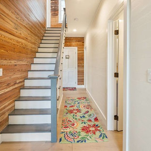 Example of a coastal painted straight wood railing staircase design in Miami with painted risers