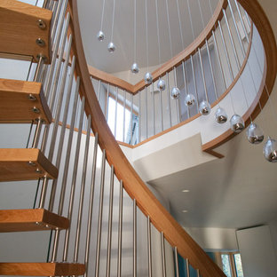 Example of a mid-sized trendy wooden curved metal railing staircase design in Buckinghamshire with glass risers