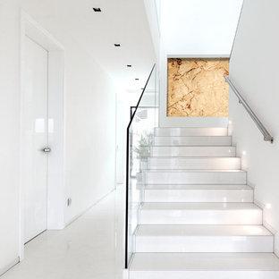 他の地域の中サイズのモダンスタイルのおしゃれな折り返し階段 (ガラスの蹴込み板) の写真