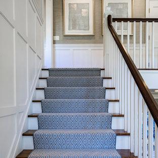 マイアミの大きいカーペット敷きのトランジショナルスタイルのおしゃれなかね折れ階段 (木の蹴込み板、木材の手すり) の写真