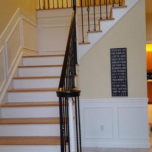 ニューヨークの中サイズのフローリングのトラディショナルスタイルのおしゃれなかね折れ階段 (木の蹴込み板) の写真