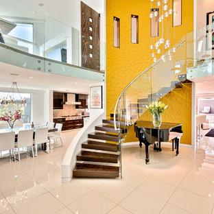 Imagen de escalera suspendida, actual, de tamaño medio, sin contrahuella, con escalones de madera y barandilla de vidrio