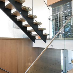 Bild på en funkis flytande trappa i trä, med öppna sättsteg och räcke i glas