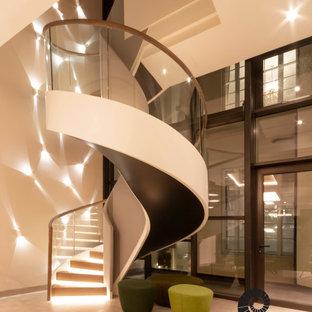 Ispirazione per una scala a chiocciola minimalista con pedata in legno, alzata in legno e parapetto in vetro