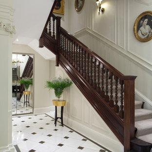 ロンドンのカーペット敷きのトラディショナルスタイルのおしゃれなかね折れ階段 (カーペット張りの蹴込み板) の写真